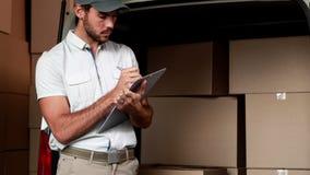 Motorista da entrega que verifica sua lista vídeos de arquivo