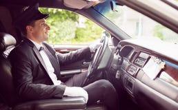 Motorista da limusina que conduz e que sorri Fotografia de Stock