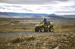 Motorista de ATV no quadrilátero amarelo nos interiores de Islândia Fotos de Stock Royalty Free