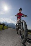 Motorista de la montaña con el sol Fotografía de archivo libre de regalías