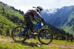 Motorista de la montaña en rce en declive Foto de archivo libre de regalías