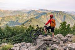 Motorista de la montaña que mira la opinión sobre rastro de la bici en montañas del otoño Foto de archivo
