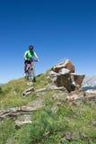 Motorista de la montaña que monta cuesta abajo en las montañas suizas Imagenes de archivo