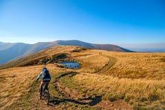 Motorista de la montaña que monta la bici imagenes de archivo