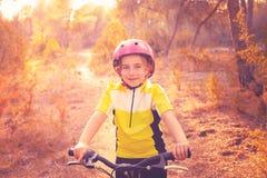Motorista de la muchacha del niño en la bici de montaña MTB fotos de archivo libres de regalías