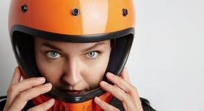 Motorista de la muchacha en una chaqueta y un casco negros Fotografía de archivo libre de regalías