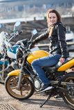 Motorista de la mujer joven que se sienta en su bici de la calle y que mira la cámara Imágenes de archivo libres de regalías