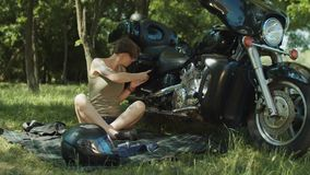 Motorista de la mujer que busca para las piezas de la motocicleta en línea almacen de video