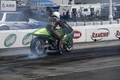Motorista de motocicleta que faz um fumo mostrar na trilha Fotografia de Stock Royalty Free