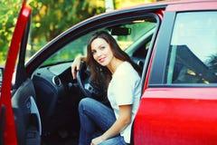 Motorista de sorriso bonito da jovem mulher atrás do carro do vermelho da roda Fotos de Stock