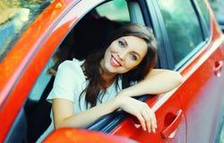 Motorista de sorriso bonito da mulher atrás do carro do vermelho da roda Imagem de Stock