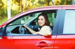 Motorista de sorriso da mulher do retrato atrás do carro do vermelho da roda Imagens de Stock Royalty Free