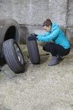 Motorista de sorriso novo da mulher que substitui pneus Fotografia de Stock