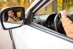 Motorista de sorriso refletido no espelho de carro foto de stock