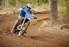 Motorista do motocross que acelera o velomotor no autódromo Fotografia de Stock