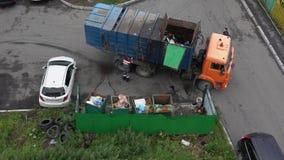 Motorista do recipiente da carga do caminhão de lixo com lixo em seus escaninhos video estoque