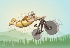 Motorista en declive de la montaña a partir de la era principal Freeriding que hace truco del superhombre en la bici en declive e Imagen de archivo libre de regalías