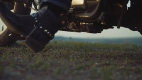 Motorista, en el fondo de la puesta del sol, mirando en la distancia entusiasta de viajar en una bici almacen de metraje de vídeo