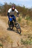 Motorista en la raza del downhil Foto de archivo libre de regalías