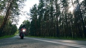Motorista en un casco que monta una motocicleta en un camino almacen de metraje de vídeo