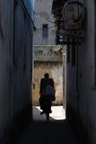 Motorista en una calle estrecha en una ciudad Imagen de archivo
