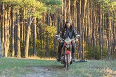 Motorista en una chaqueta de cuero y casco en una motocicleta retra en el bosque imagenes de archivo