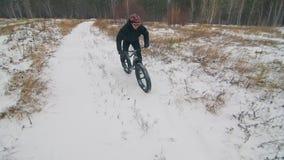 Motorista extremo profesional del deportista que monta la bici gorda en aire libre El paseo del ciclista en invierno en el campo  metrajes