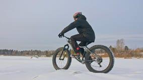 Motorista extremo profesional del deportista que monta una bici gorda en aire libre Paseo del ciclista en el invierno en el hielo almacen de metraje de vídeo
