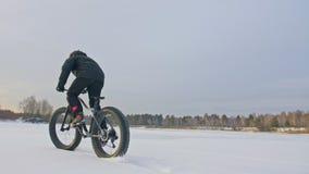 Motorista extremo profesional del deportista que monta una bici gorda en aire libre Paseo del ciclista en el invierno en el hielo metrajes