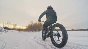 Motorista extremo profesional del deportista que monta una bici gorda en aire libre Paseo del ciclista en el invierno en el hielo almacen de video