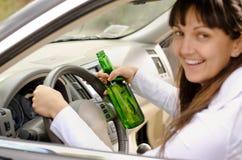 Motorista fêmea que bebe e que conduz foto de stock