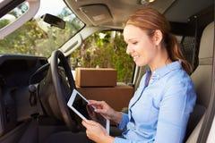 Motorista fêmea Sitting In Van Using Digital Tablet da entrega Fotografia de Stock Royalty Free