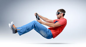 Motorista farpado engraçado do homem nos óculos de proteção com um volante, auto conceito Foto de Stock Royalty Free