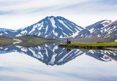 Motorista feliz en el contexto del lago y las montañas que nievan en Islandia Imagenes de archivo