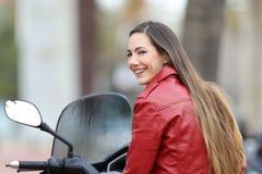 Motorista feliz que le mira en una moto Imagenes de archivo