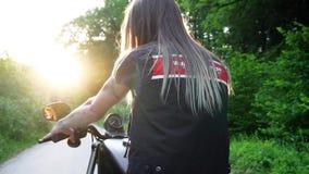 Motorista femenino caliente con los tatuajes que se sientan en su bici y que celebran un manillar listo para montar Ciérrese para metrajes