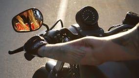 Motorista femenino caucásico con los tatuajes que se sientan en su bici y que celebran un manillar Ciérrese para arriba de mujer  metrajes