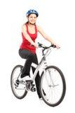 Motorista femenino con el casco que presenta al lado de una bici Fotos de archivo libres de regalías