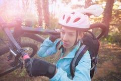 Motorista femenino de la montaña que lleva su bicicleta en bosque Foto de archivo