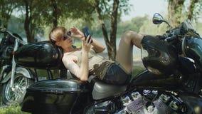 Motorista femenino elegante que se relaja con el teléfono en la bici almacen de metraje de vídeo