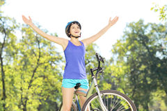 Motorista femenino feliz con las manos aumentadas en una bici al aire libre Foto de archivo libre de regalías