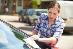 Motorista femenino frustrado que mira la multa de aparcamiento imagen de archivo