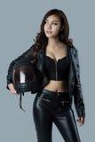 Motorista femenino hermoso que lleva una chaqueta de cuero Imagenes de archivo