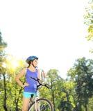 Motorista femenino joven que presenta en una bici de montaña el día soleado Imagen de archivo libre de regalías
