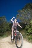 Motorista femenino que derrama el agua sobre cara Imagenes de archivo