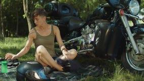 Motorista femenino que repara el motor de la moto en parque almacen de metraje de vídeo