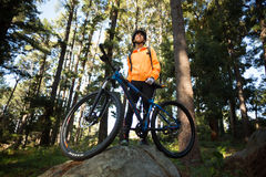 Motorista femenino que se coloca con la bici de montaña en bosque Fotografía de archivo