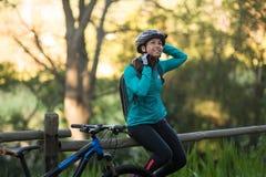 Motorista femenino que se sienta en una cerca y que quita el casco de la bicicleta Foto de archivo libre de regalías