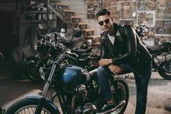 motorista hermoso joven en chaqueta de cuero negra con las motos clásicas fotografía de archivo libre de regalías