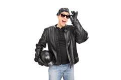 Motorista joven con las gafas de sol y la chaqueta de cuero Imagenes de archivo